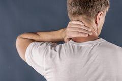 Uomo che tiene il suo collo nel dolore su fondo blu Dolore al collo più basso Uomo senza camicia che tocca il suo collo per il do immagini stock
