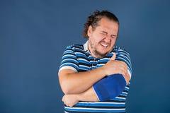 Uomo che tiene il suo gomito irritato Problemi sanitari fotografia stock libera da diritti