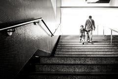 Uomo che tiene il suo nipote che cammina sulla scala della stazione della metropolitana fotografia stock libera da diritti