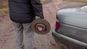 Uomo che tiene il vecchio disco del freno vicino all'automobile stock footage