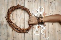 Uomo che tiene Jesus Crown Thorns con la sua mano e molte manette fotografia stock