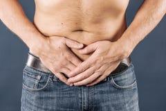 Uomo che tiene la sua uretra nel dolore Uomo con dolore nudo dell'uretra di esperienza del torso su fondo blu Concetto MEDICO immagine stock libera da diritti