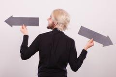 Uomo che tiene le frecce nere che indicano a destra e a sinistra Fotografia Stock