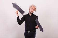 Uomo che tiene le frecce nere che indicano a destra e a sinistra Fotografia Stock Libera da Diritti
