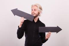 Uomo che tiene le frecce nere che indicano a destra e a sinistra Fotografie Stock