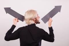 Uomo che tiene le frecce nere che indicano a destra e a sinistra Fotografie Stock Libere da Diritti