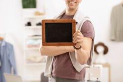 Uomo che tiene mini lavagna in atelier fotografia stock