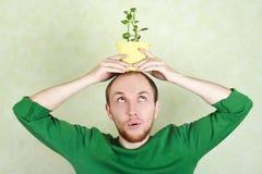Uomo che tiene pianta conservata in vaso sulla sua testa Fotografia Stock