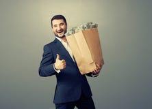 Uomo che tiene sacco di carta con soldi Fotografie Stock