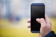 Uomo che tiene Smartphone contro il fondo verde Immagini Stock
