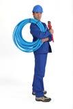 Uomo che tiene tubo blu Immagine Stock