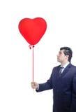 Uomo che tiene un aerostato rosso Fotografia Stock