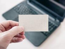 Uomo che tiene un biglietto da visita in bianco del cartone e che per mezzo del computer portatile Immagini Stock Libere da Diritti