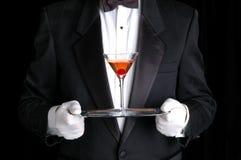 Uomo che tiene un cocktail sul cassetto d'argento Immagini Stock