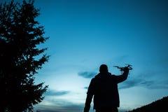 Uomo che tiene un fuco per fotografia aerea Siluetta contro la t Immagine Stock