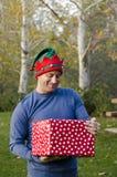 Uomo che tiene un regalo di Natale fuori Fotografia Stock Libera da Diritti