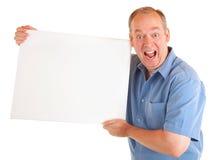 Uomo che tiene un segno bianco in bianco Fotografia Stock