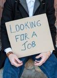 Uomo che tiene un segno che dice sto cercando un lavoro Immagine Stock Libera da Diritti