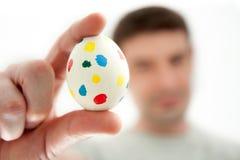 Uomo che tiene un uovo di Pasqua Chiazzato Immagini Stock Libere da Diritti
