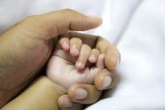 Uomo che tiene una mano del bambino Fotografia Stock