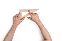Uomo che tiene una squadra a triangolo di legno Fotografia Stock Libera da Diritti