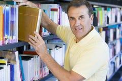 Uomo che tira un libro delle biblioteche fuori dalla mensola Fotografia Stock Libera da Diritti