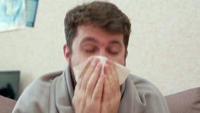 Uomo che tossisce in un fazzoletto di carta Ha il raffreddore, emicrania, febbre, brividi stock footage