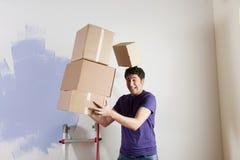 Uomo che trasporta le caselle impilate Fotografia Stock