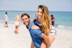 Uomo che trasporta sulle spalle amica contro gli amici alla spiaggia Fotografia Stock