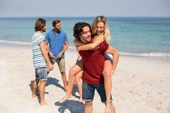 Uomo che trasporta sulle spalle amica dagli amici alla spiaggia Fotografia Stock Libera da Diritti