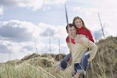 Uomo che trasporta sulle spalle donna sulla spiaggia Fotografia Stock Libera da Diritti