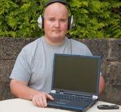 Uomo che usando computer portatile e voip Fotografie Stock Libere da Diritti