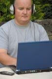 Uomo che usando computer portatile e voip Fotografia Stock Libera da Diritti