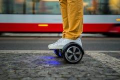 Uomo che usando hoverboard contro lo sfondo del tram Fotografia Stock Libera da Diritti