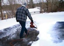 Uomo che usando il ventilatore di foglia per rimuovere neve dalla strada privata fotografia stock