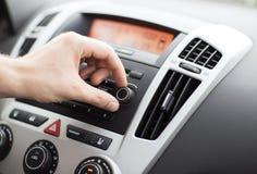 Uomo che usando l'audio sistema stereo dell'automobile Immagini Stock
