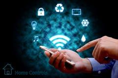 Uomo che usando la tavola calda domestica online di controllo domestico a distanza o dello Smart Phone immagini stock