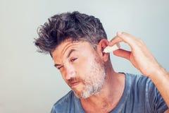 Uomo che usando le gocce dell'orecchio su fondo bianco fotografie stock libere da diritti