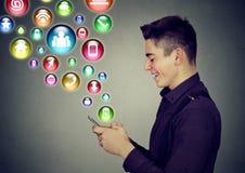 Uomo che usando le icone dell'applicazione sociali di media dello smartphone che vengono fuori schermo Fotografie Stock Libere da Diritti