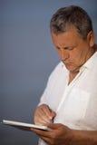 Uomo che usando penna sul computer tenuto in mano della compressa Immagine Stock