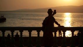 Uomo che usando Smartphone dal mare il turista cammina lungo la passeggiata fotografia stock footage