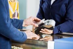 Uomo che usando tecnologia di NFC al contatore di concessione Immagini Stock Libere da Diritti