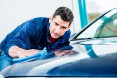 Uomo che usando un asciugamano assorbente per l'essiccamento della superficie di un'automobile immagine stock libera da diritti