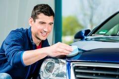 Uomo che usando un asciugamano assorbente per l'essiccamento della superficie di un'automobile fotografia stock
