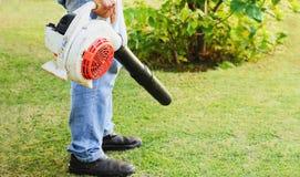 Uomo che usando un ventilatore di foglia sul prato inglese del giardino fotografie stock