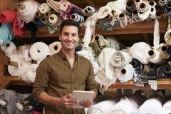 Uomo che utilizza compressa nel magazzino di stoccaggio del tessuto, ritratto Immagine Stock
