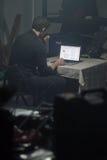 Uomo che utilizza computer portatile nella stanza scura Fotografia Stock
