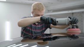 Uomo che utilizza il dispositivo di lucidatura mentre prendendo cura dell'automobile nel garage stock footage