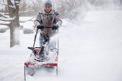 Uomo che utilizza sgombraneve a turbina nella neve profonda Fotografie Stock