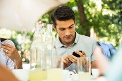 Uomo che utilizza smartphone mentre sedendosi nel ristorante all'aperto Fotografia Stock Libera da Diritti